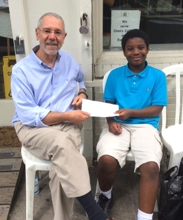 Aiden Rahaim giving his donation to CDI's Executive Director, John Mancuso
